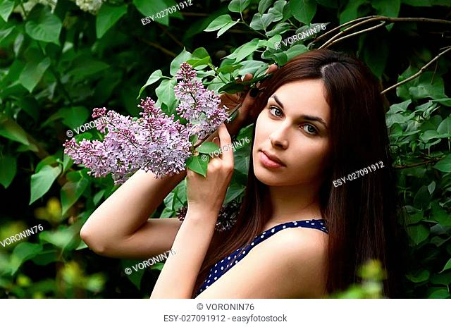 The beautiful woman with flowers of lilac