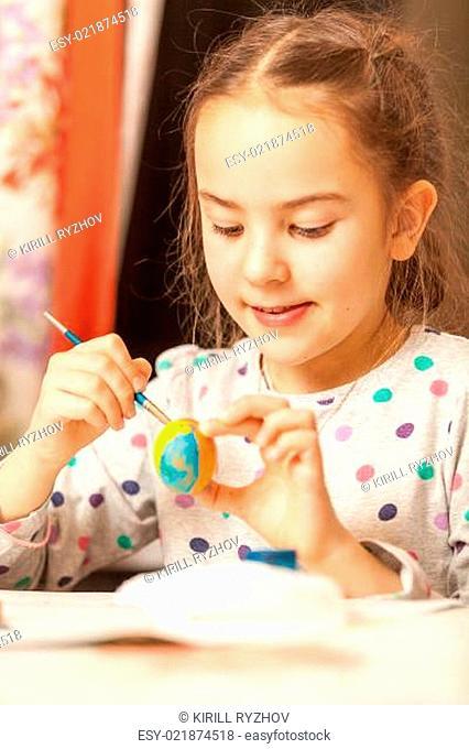 Portrait of girl painting easter eggs