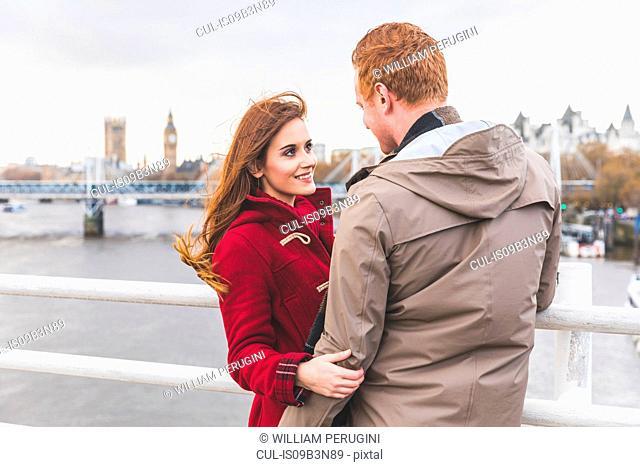 Couple hugging on bridge over the Thames, London, UK