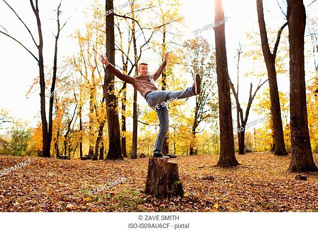 Teenage boy balancing on tree stump in autumn forest