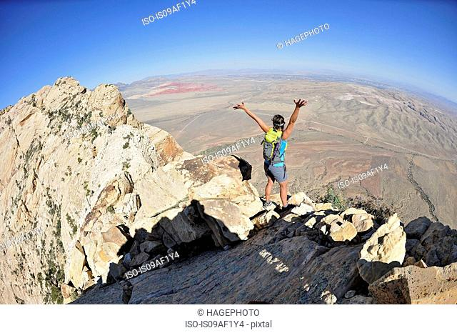Female hiker celebrating on ridge, Mount Wilson, Red Rock Canyon, Nevada, USA