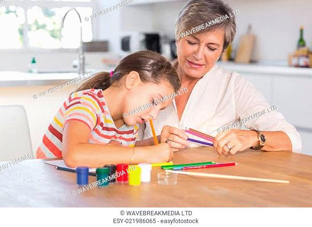 Child drawing with her grandmother
