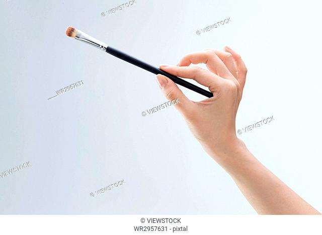 A hand holding a brush