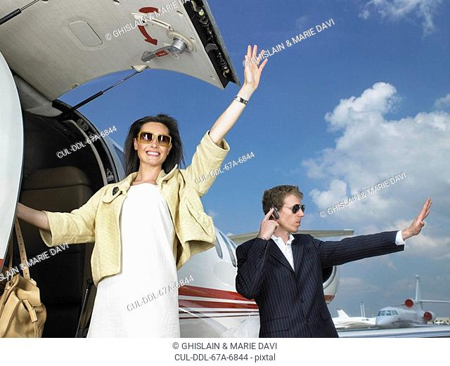 Woman exiting plane waving with bodyguard