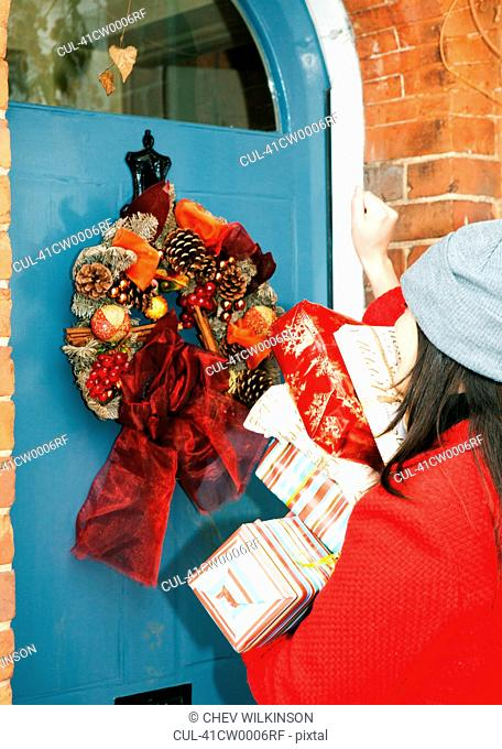 Woman with wrapped gifts at front door