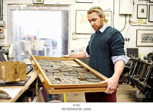 Young man carrying letterpress tray in traditional print workshop