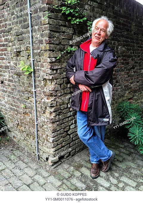 Tilburg, Netherlands. Elder vicar of pastor leaning on a century old wall in a museum's garden