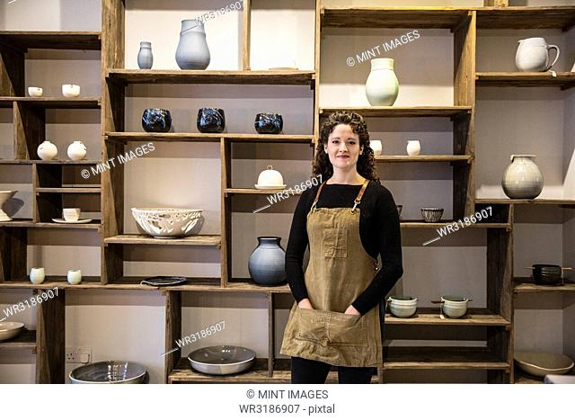 Woman with curly brown hair wearing apron standing in her pottery shop, smiling at camera