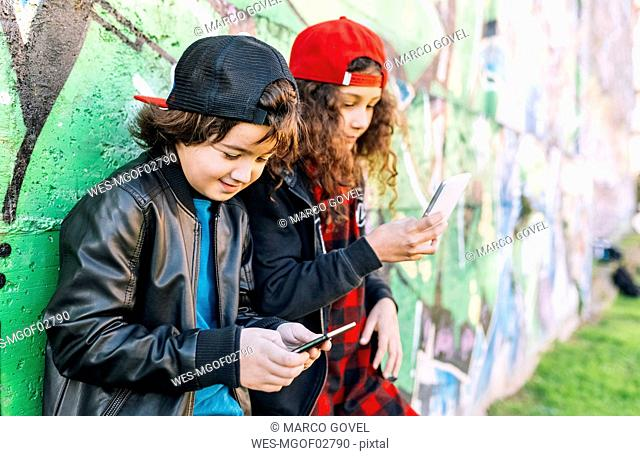 Two children leaning against graffiti wall using smartphones