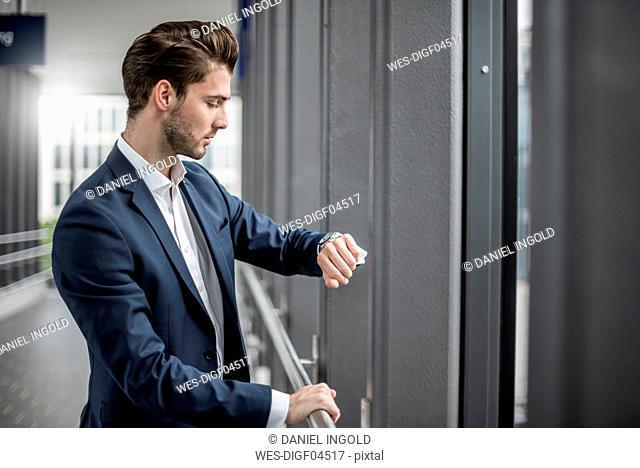 Businessman in a passageway checking the time