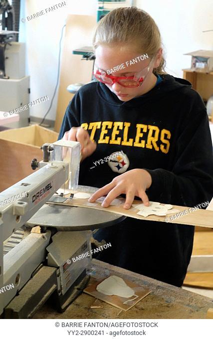 6th Grade Girl Using Scroll Saw in Technology Class, Wellsville, New York, USA