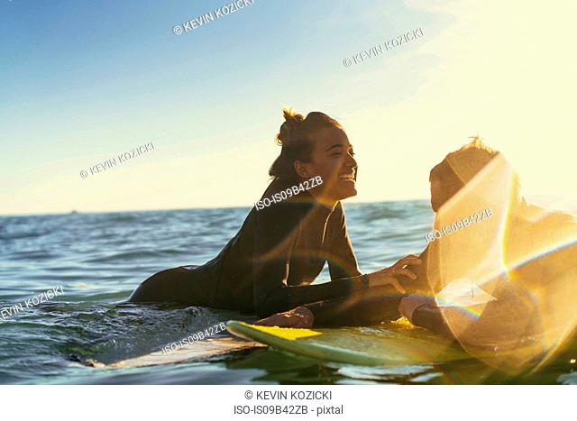 Surfing couple leaning on surfboards in sea, Newport Beach, California, USA