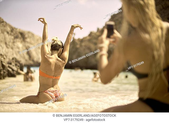 woman taking photo with smartphone of friend in sand at Seitan Limania Beach, Crete, Greece