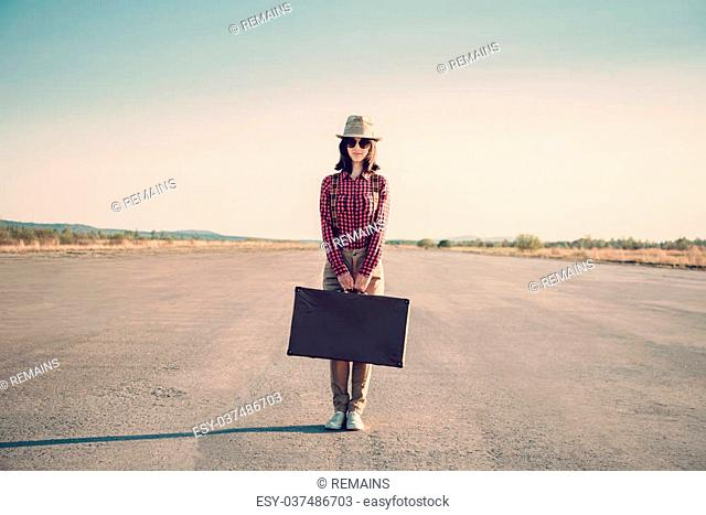 Traveler hipster woman stands on road with vintage suitcase, space for text