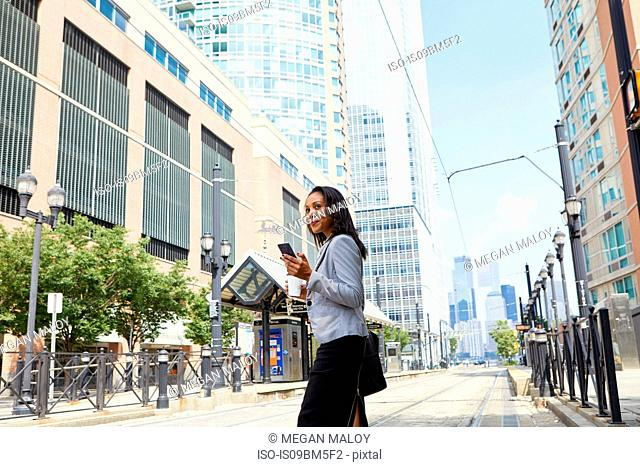 Businesswoman crossing light rail tracks