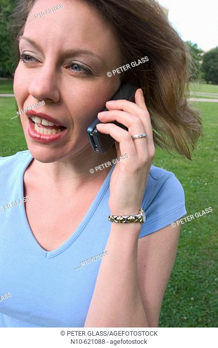 Young woman, standing on the grass at a park, talking on her cell phone