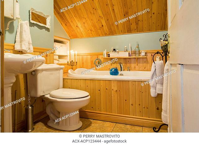 White therapeutic bathtub encased in a pinewood vertical plank base, toilet and pedestal sink in main bathroom with ceramic tile flooring on upstairs floor...