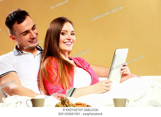 shopping consumerism leisure and people concept. young couple with tablet pc and credit card on sofa at home,doing shopping on the internet