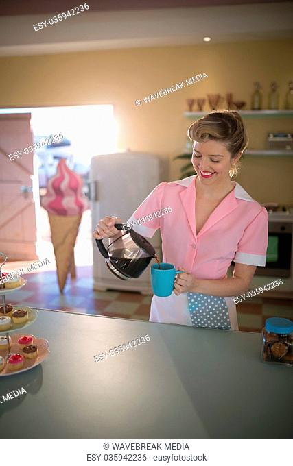 Waitress pouring black coffee in mug at restaurant