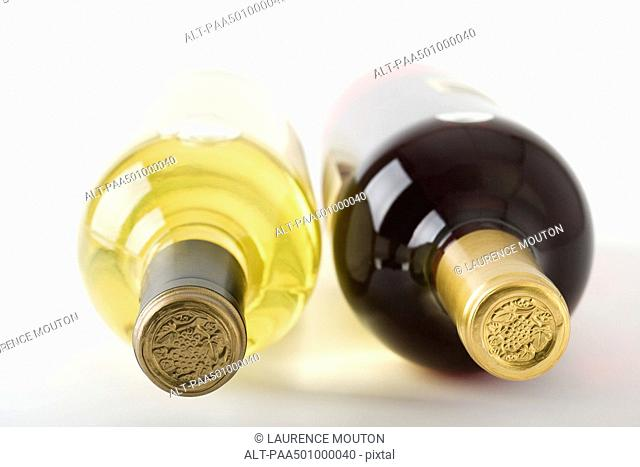 Bottles of red and white wine lying on their sides, close-up