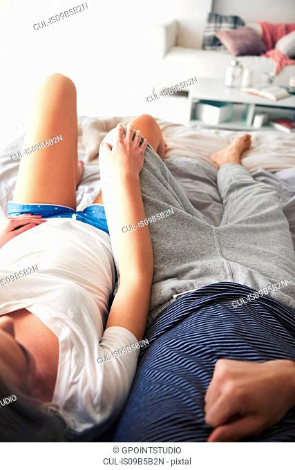 Couple lying on bed, relaxing, elevated view