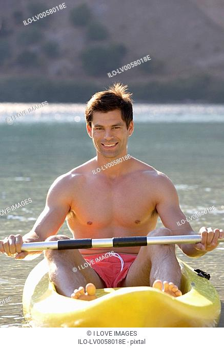 A man canoeing on a lake