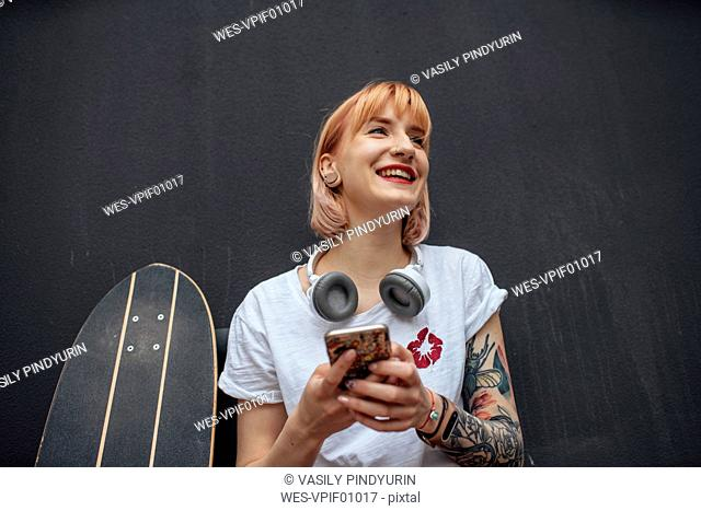 Happy young woman with skateboard, headphones and cell phone