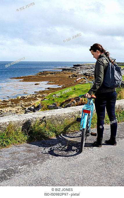 Young woman standing with bicycle beside sea wall, Inishmore, Ireland