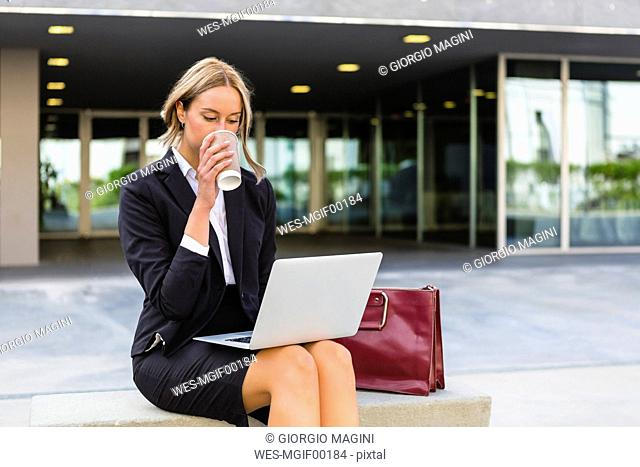 Businesswoman with fashionable leatherbag and coffee to go sitting on bench looking at laptop