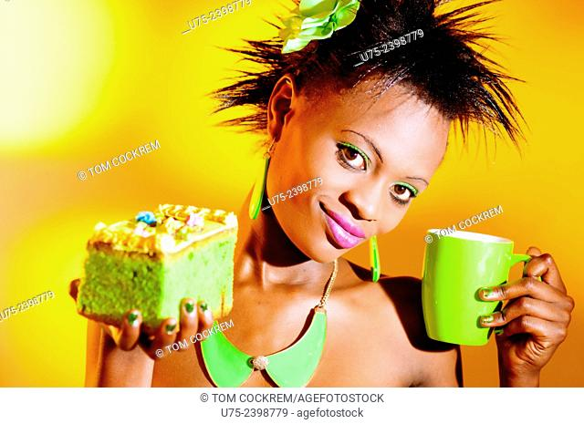 Young Kenyan woman with cake and cup in studio setting