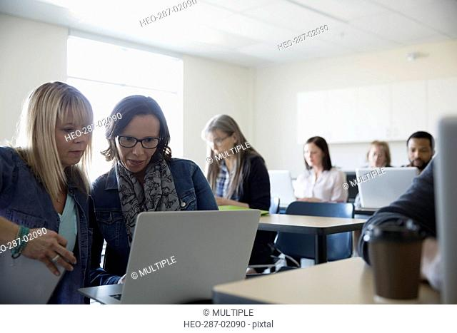 Adult education students using laptop in classroom