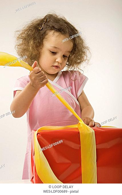 Girl 2-3 unwrapping present, portrait