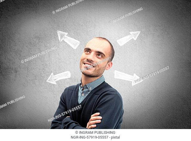 Confident, young businessman looking at chalk drawn arrows on a concrete wall
