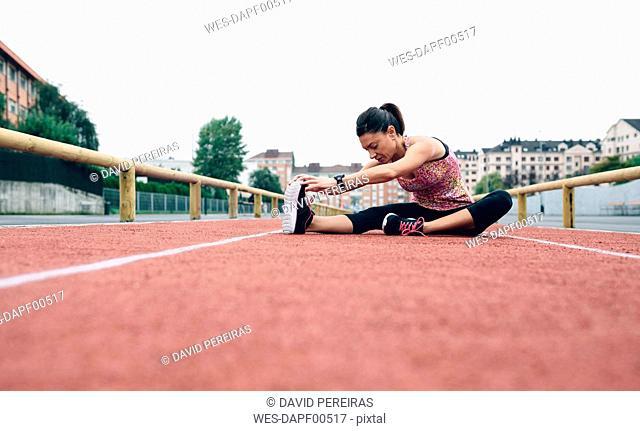 Woman stretching on tartan track