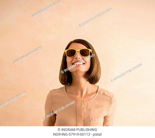 Portrait of beautiful smiling young woman wearing sunglasses. Lots of copyspace