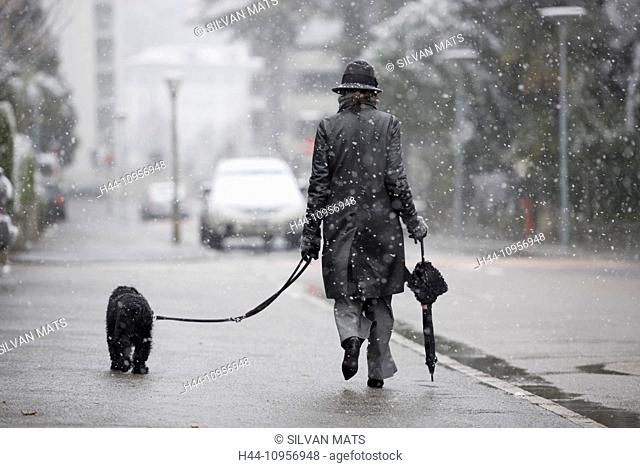 Woman walking on the street when in it's snowing with a umbrella and a dog in locarno ticino Switzerland, Europe
