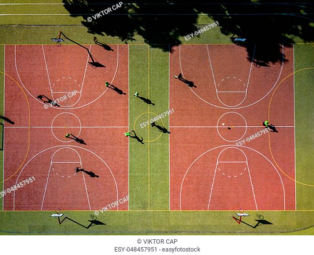 Aerial view of a soccer pitch with people playing soccer on it - in warm morning sun, casting long shadows