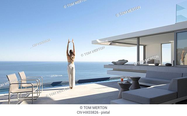 Woman practicing yoga mountain pose on sunny modern, luxury home showcase exterior patio with ocean view