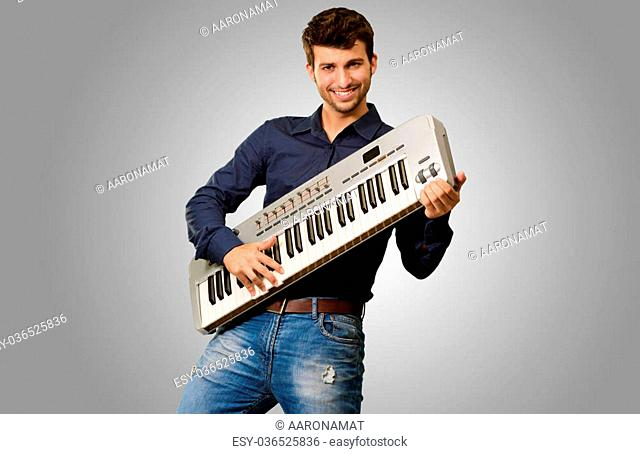 Young Man Holding Piano Isolated On Grey Background