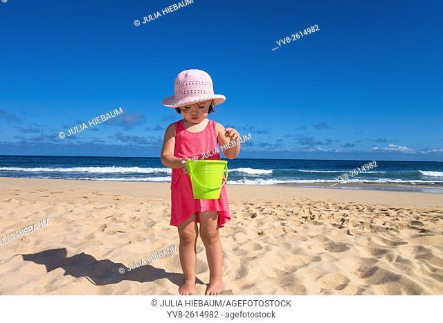 Toddler girl holding a green bucket at the beach, Kauai island