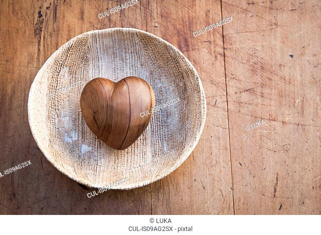 Still life of heart shaped wooden object in wooden bowl