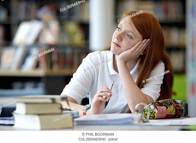 Portrait of teenage girl daydreaming in library