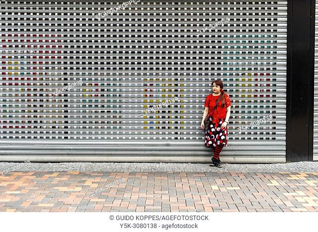 Amsterdam, Netherlands. Young, redhaired woman leaning against a store window shutter and fence. Stores usually use these fences and blinds to protect against...