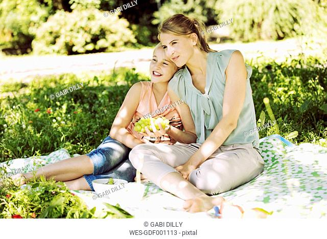 Girl and young woman sitting together on blanket in a park watching something