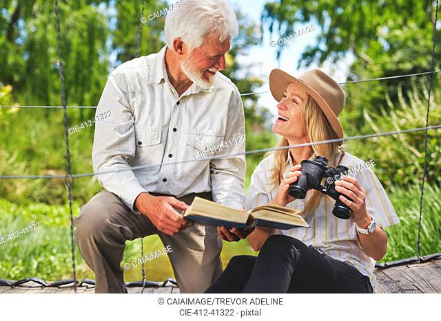 Smiling active senior couple bird watching with binoculars and book