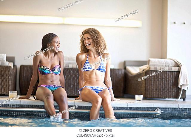 Two young women chatting on edge of spa swimming pool