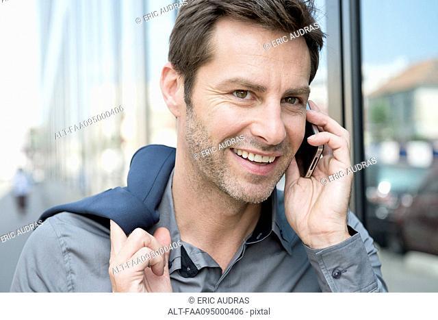 Mature man making phone call using smartphone