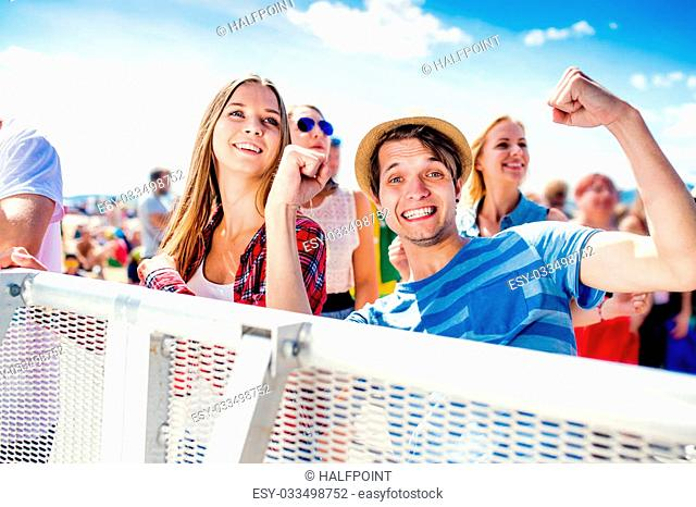 Teenagers at summer music festival under the stage in a crowd enjoying themselves, boy showing peace sign