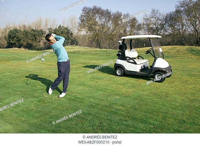 Golfer on a golf course, golf cart