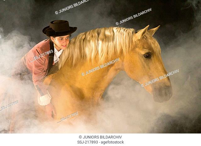 Lusitano. Girl in traditional dress fondling a palomino gelding at night. Portugal